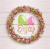 Festlicher Zweig-Kranz Ostern mit Blumen auf hölzernem Hintergrund Stockbild