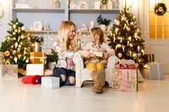 Festliches Bild der Mutter und der Tochter, die auf Stuhl im Hintergrund des Weihnachtsbaums sitzen Stockfotos