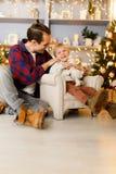 Festliches Bild des Jungen auf Stuhl und des glücklichen Vatis Lizenzfreie Stockbilder