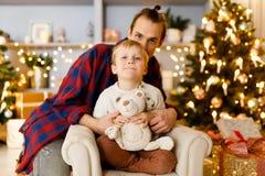 Festliches Bild des Vaters, der seinen Sohn sitzt auf Stuhl umfasst Lizenzfreie Stockfotografie