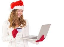 Festliches blondes Einkaufen online mit Laptop Stockfoto