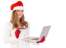 Festliches blondes Einkaufen online mit Laptop Stockfotografie