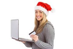 Festliches blondes Einkaufen online mit Laptop Stockfotos