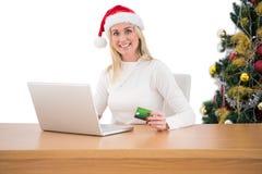 Festliches blondes Einkaufen online mit Laptop Lizenzfreies Stockfoto
