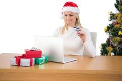 Festliches blondes Einkaufen online mit Laptop Lizenzfreie Stockbilder