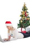 Festliches blondes Einkaufen online mit Laptop Lizenzfreie Stockfotografie