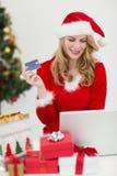 Festliches blondes Einkaufen online mit Laptop Stockbild