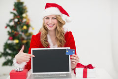 Festliches blondes Einkaufen online mit Laptop und dem Zeigen auf es Lizenzfreie Stockbilder