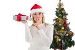 Festliches blondes haltenes Geschenk durch den Baum Stockbild