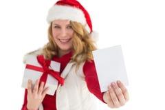 Festliches blondes haltenes Weihnachtsgeschenk und Zeigen einer Karte Stockfotografie