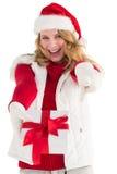 Festliches blondes haltenes Weihnachtsgeschenk und Zeigen ihres Fingers Lizenzfreies Stockbild