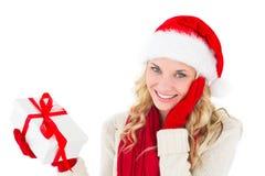 Festliches blondes Lächeln an der Kamera, die Geschenk hält Lizenzfreie Stockbilder
