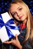 Festliches Foto des netten kleinen Mädchens mit dem langen blonden Haar, das eine Geschenkbox hält Stockfotografie