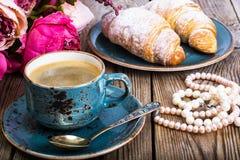 Festliches Frühstück des Espressos, des frischen Hörnchens, der Blumen und des Geschenks Lizenzfreies Stockbild
