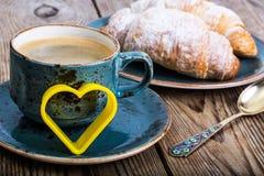 Festliches Frühstück des Espressos, des frischen Hörnchens, der Blumen und des Geschenks Lizenzfreie Stockfotografie