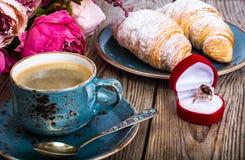 Festliches Frühstück des Espressos, des frischen Hörnchens, der Blumen und des Geschenks Stockfotos