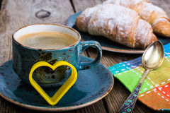 Festliches Frühstück des Espressos, des frischen Hörnchens, der Blumen und des Geschenks Stockfoto
