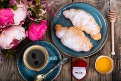 Festliches Frühstück des Espressos, des frischen Hörnchens, der Blumen und des Geschenks Lizenzfreie Stockfotos
