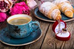 Festliches Frühstück des Espressos, des frischen Hörnchens, der Blumen und des Geschenks Stockbild