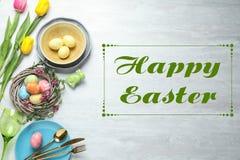 Festliches Gedeck und Text fröhliche Ostern auf hölzernem Hintergrund stockfotografie