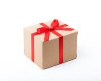 Festliches Geschenk. Beige Kasten und roter Satinbogen. Lizenzfreies Stockbild