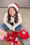 Festliches kleines Mädchen, das an der Kamera mit Geschenken lächelt Lizenzfreies Stockbild