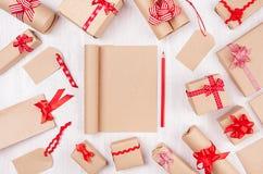 Festlig åtlöje för nytt år upp - den tomma sketchbooken för kraft papper omgav gåvor med röda pilbågar, blyertspenna på vit träba royaltyfria foton