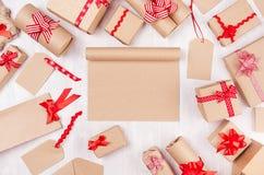 Festlig åtlöje för nytt år upp - den tomma sketchbooken för kraft papper omgav gåvor med röda pilbågar på vit träbakgrund arkivfoton