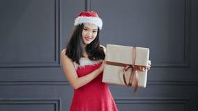 Festlig asiatisk kvinnlig bärande Santa Claus för medelskott som dräkt ler och rymmer gåva på studion