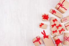 Festlig bakgrund för jul - olika gåvaaskar av kraft papper och röda band, pilbågar som gränsen på mjukt vitt träbräde royaltyfri fotografi