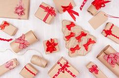 Festlig bakgrund för jul - olika gåvaaskar av kraft papper, tomma etiketter och röda band, pilbågar på mjukt vitt träbräde royaltyfri bild