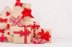 Festlig bakgrund för nytt år - kraft gåvaaskar med röda pilbågar och band och closeup för julträd på det vita träbrädet royaltyfri fotografi