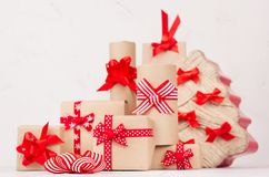 Festlig bakgrund för nytt år - kraft gåvaaskar med röda pilbågar och band och julträd på det vita träbrädet arkivbild