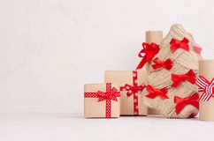 Festlig bakgrund för nytt år - kraft gåvaaskar med röda pilbågar och band och julträd på det vita träbrädet royaltyfri fotografi