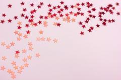 Festlig bakgrund för pastellfärgade rosa färger med metalliska konfettier royaltyfri foto