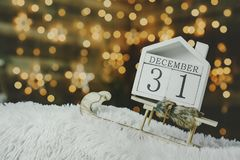 Festlig bakgrund på helgdagsaftonen av det nya året, med en nedräkningkalender på December 31 på bakgrunden av lysande royaltyfria foton