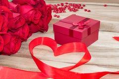 Festlig bakgrund till valentin dag En bukett av röda rosor, en gåvaask, enformad stearinljus och ett rött band med en hjärta arkivbilder