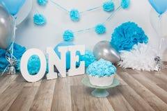 Festlig bakgrundsgarnering för födelsedagberöm med den gourmet- kakan, bokstäver som säger en, och blått sväller i studio royaltyfri bild