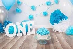 Festlig bakgrundsgarnering för födelsedagberöm med den gourmet- kakan, bokstäver som säger en, och blått sväller i studio Fotografering för Bildbyråer