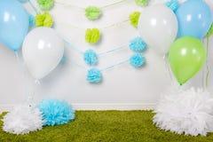 Festlig bakgrundsgarnering för första födelsedagberöm eller easter ferie med blått-, gräsplan- och vitbokblommor, ballonger Royaltyfria Foton