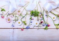 Festlig blommasammansättning på den vita träbakgrunden Över huvudet sikt Royaltyfri Bild