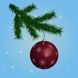 Festlig boll som hänger på julträdet, blå bakgrund med snöflingor Arkivfoto