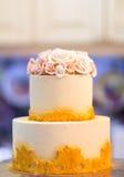 Festlig bröllopstårta med blommor, guling-apelsin blommor, brits, härligt som är försiktig royaltyfria foton