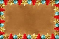 Festlig brun bakgrund för jul eller för nytt år med en ram som göras av julleksaker arkivbilder