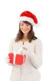 Festlig brunett i den santa hatten som öppnar en gåva Arkivfoton