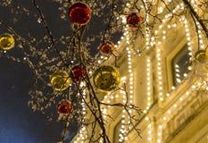 Festlig garnering för gata av staden för jul och ljusa skinande bollar för nytt år av guld- rött på träd Royaltyfri Fotografi