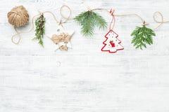 Festlig girland av julgarneringar och barrträdfilialer på vit bakgrund royaltyfria bilder