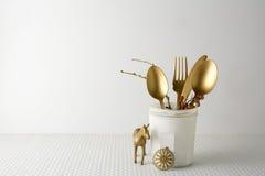Festlig guld- bestickkniv och gaffelsked i en vit flaska, ljus bakgrund Arkivfoton