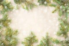 Festlig jul gränsar med granfilialer och snöflingor med snö på lantlig beige bakgrund Royaltyfria Bilder