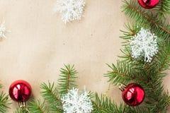 Festlig jul gränsar med röda bollar på granfilialer och snöflingor på lantlig beige bakgrund Royaltyfria Foton